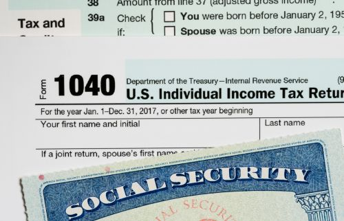 Social Security card laid on top of Form 1040 tax return of income in retirement
